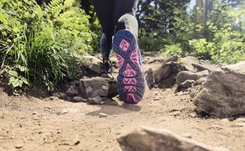 close up shot of runner trail running; bottom of shoe=focus