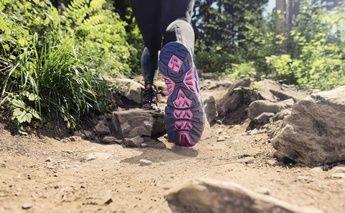 close up shot of runner trail running; bottom of shoe=focus