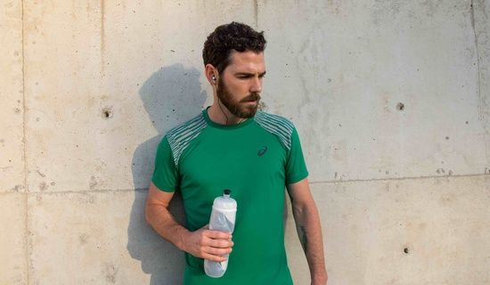 man in green shirt holding a water bottle