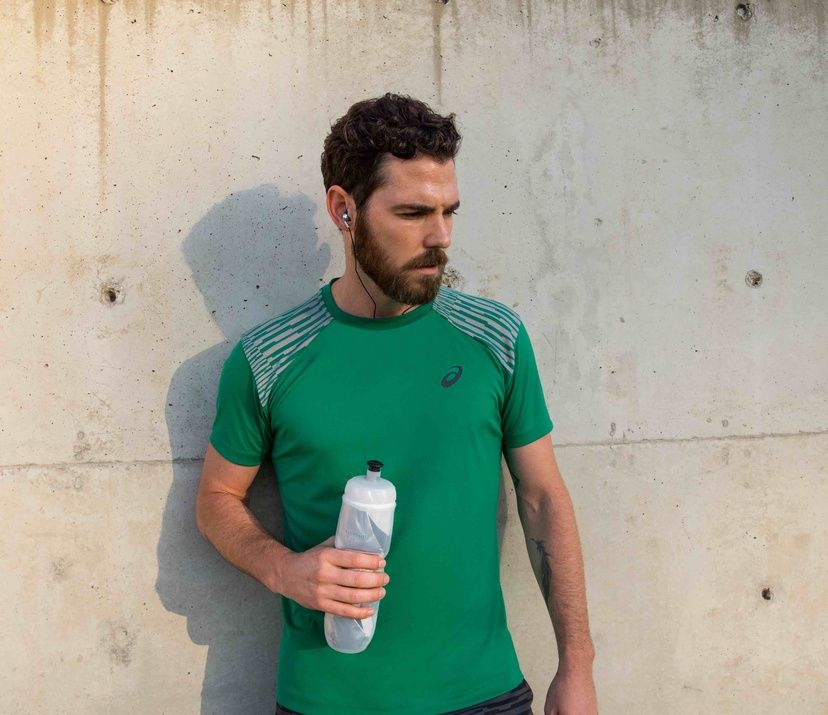 man in green shirt holding a water bottle