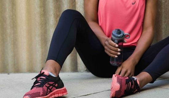 woman in pink top with pink & black running shoes & holding a waterbottle; shoes are the main focus