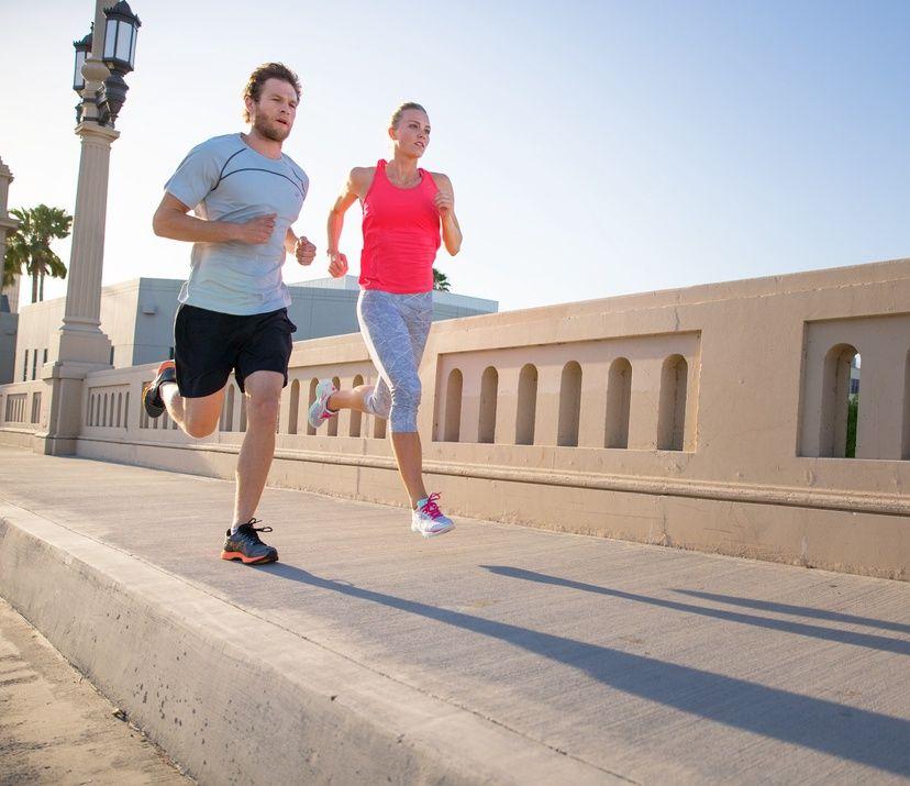man & woman street running; woman in pink top; man in grey top