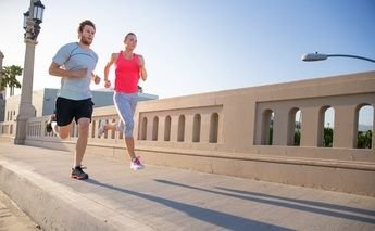 man & woman street running; woman in pink top; man in grey top
