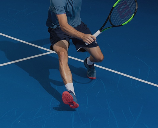 A closeup of a man on a tennis court holding a racquet, preparing to hit the ball.