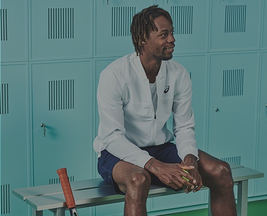 A smiling man dressed in tennis gear sitting on a bench in a turquoise locker room.