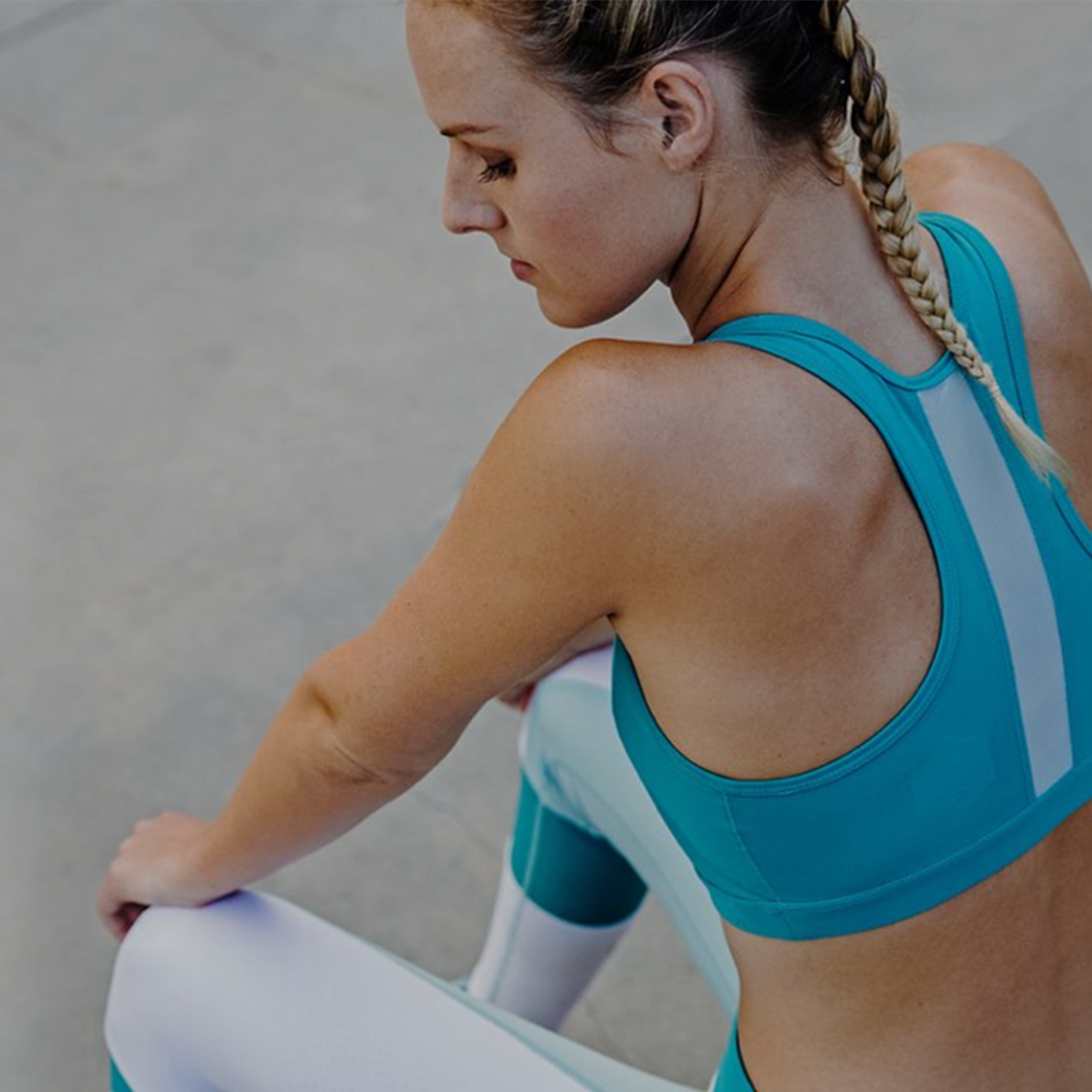 Seated woman dressed in blue and white sports bra and leggings.