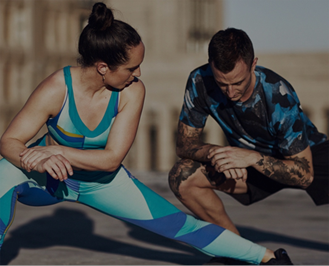 Man and woman in athletic clothing doing lunges.