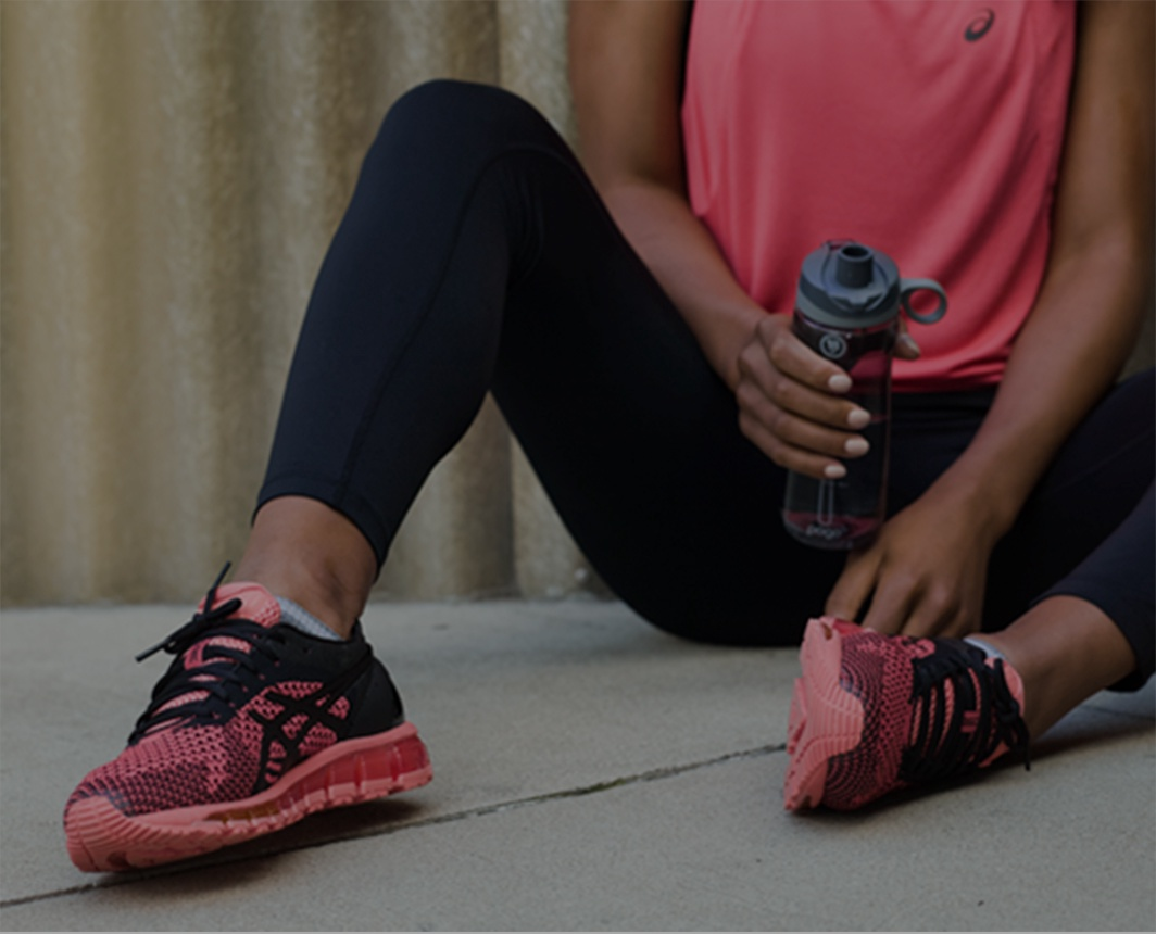 Woman in pink shoes, pink top and black leggings sitting and holding a water bottle.