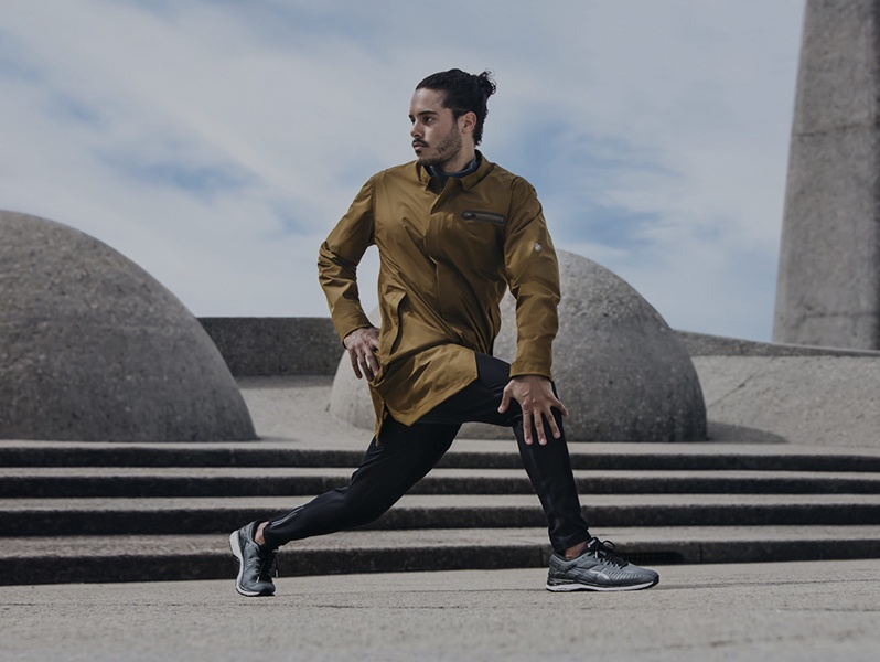 Man in a gold athletic jacket, black pants and running shoes stretching outside.
