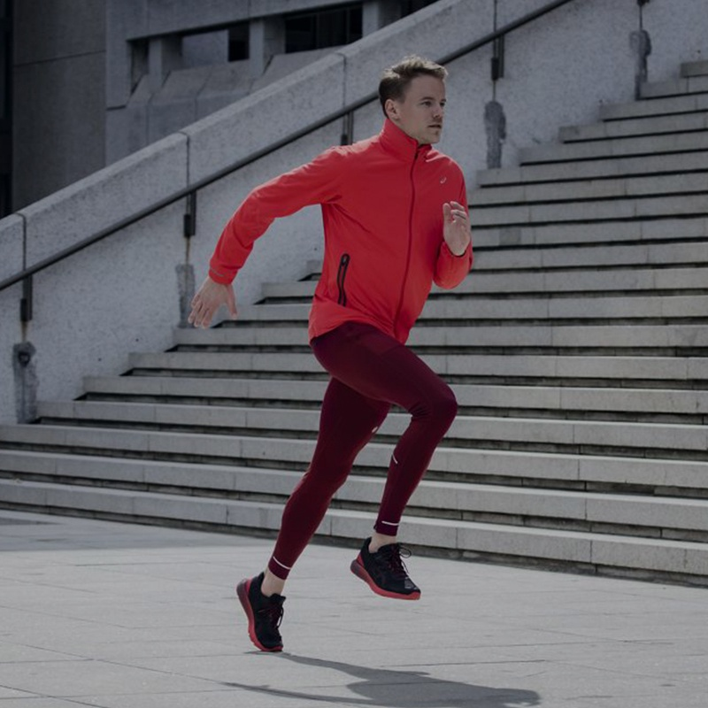 Man in red running jacket and leggings running up a flight of stairs.