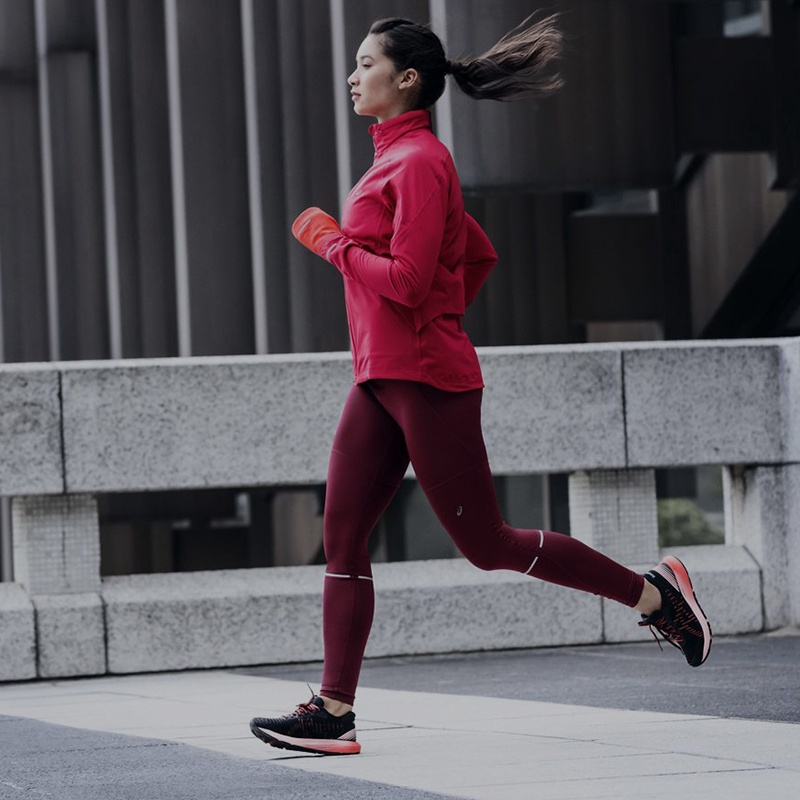 Woman running in pink running jacket and red leggings.