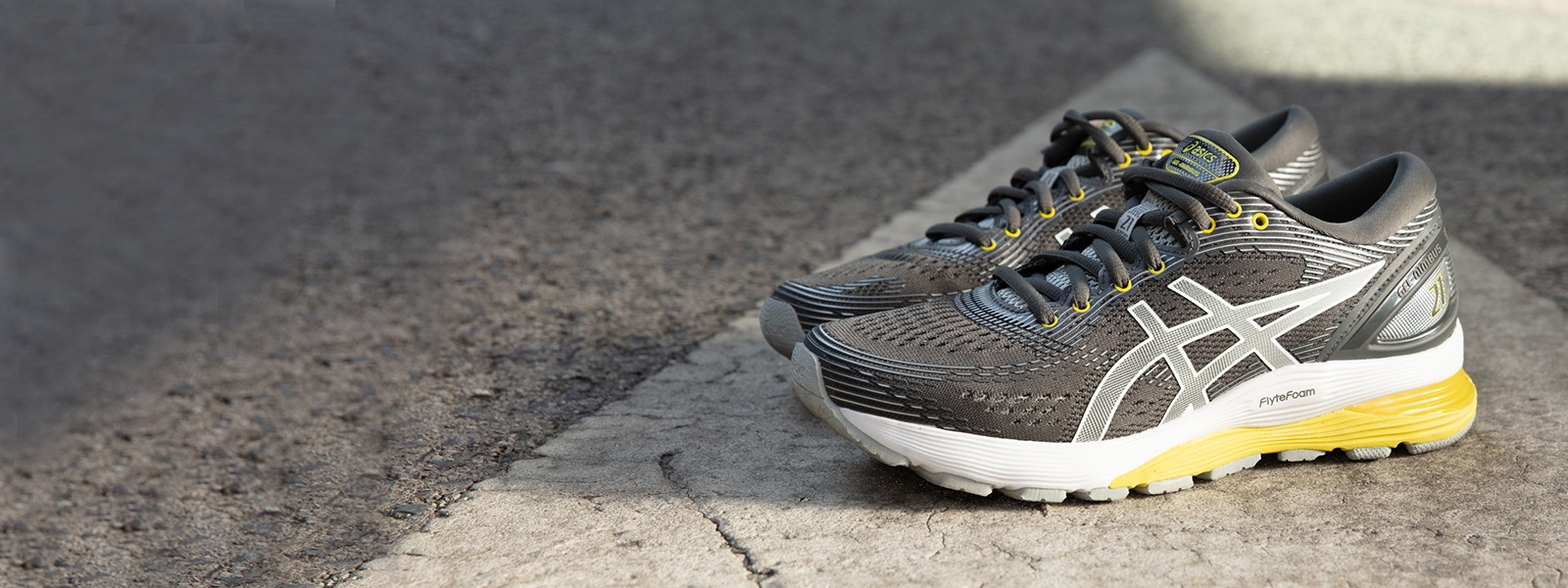 Grey and yellow running shoes sitting on a street