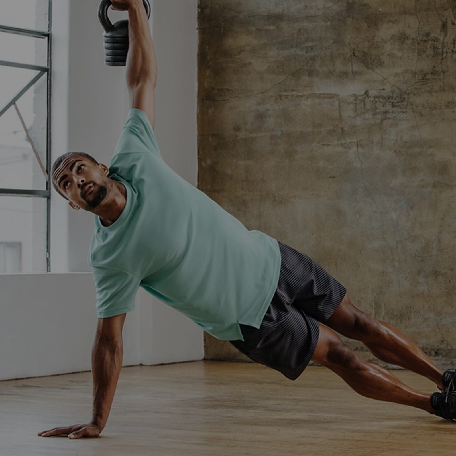 Man in a turquoise shirt and gray shorts doing a side plank.
