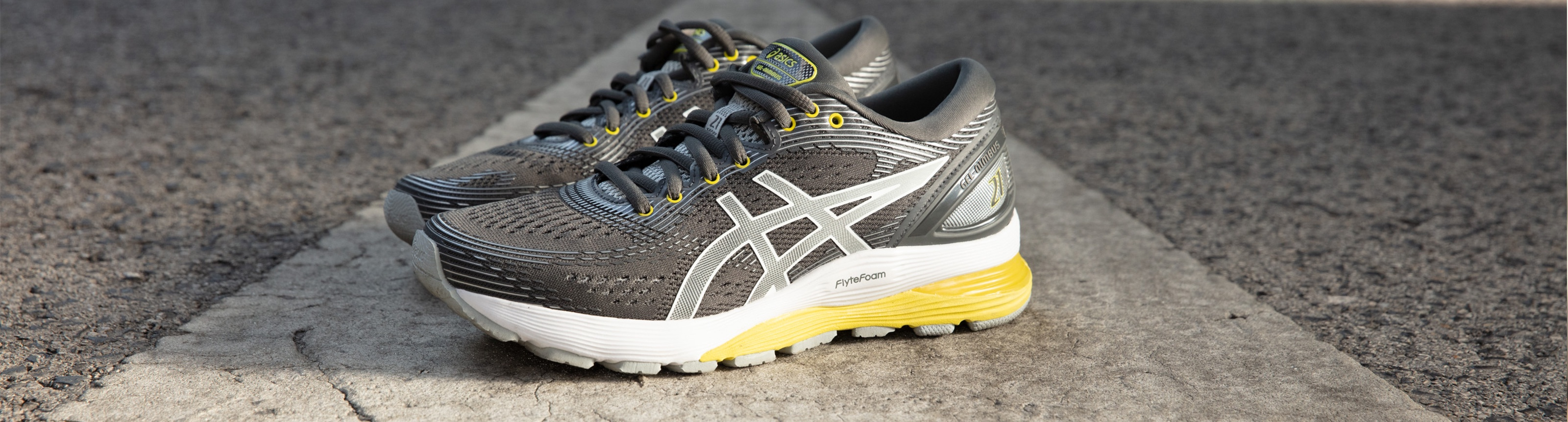 Grey and Yellow Gel-Nimbus 21 running shoes sitting on the ground