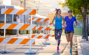two women running through streets - construction to the left of them