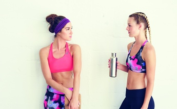 two women - talking agains wall of studio gym