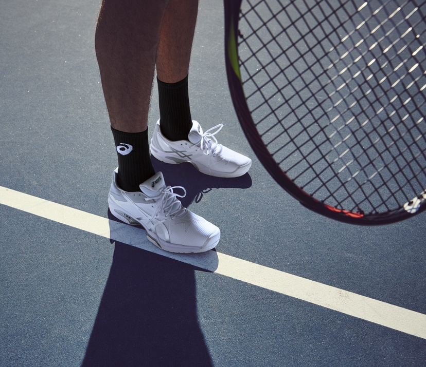 feet and racket on tennis court