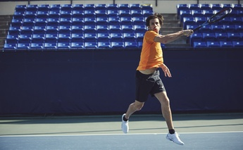 man in orange t shirt playing tennis