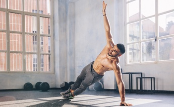 man working out in gym, arm up in air