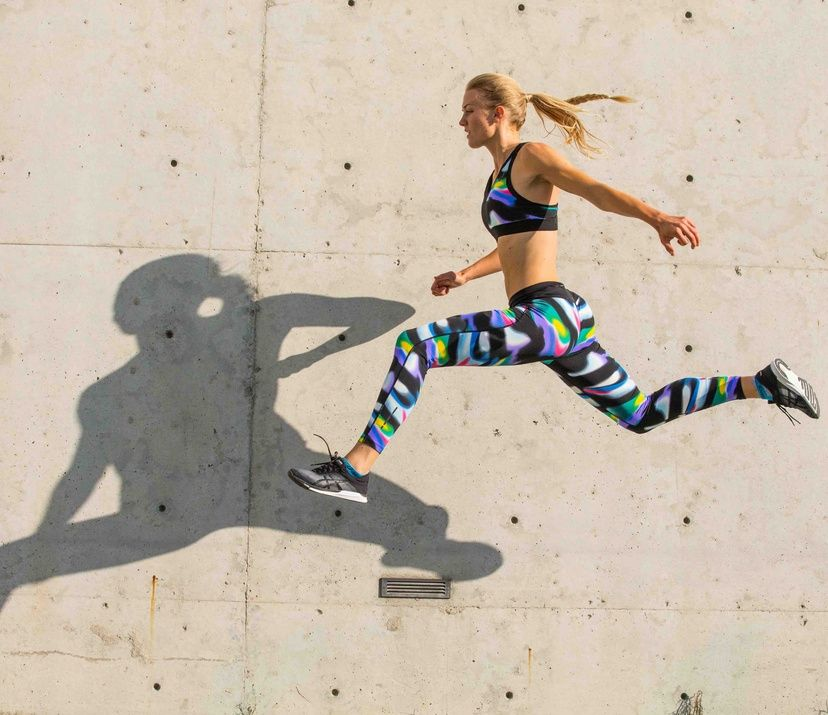 woman jumping in air; concreate background