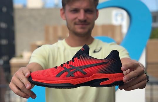 Man holding tennis shoe
