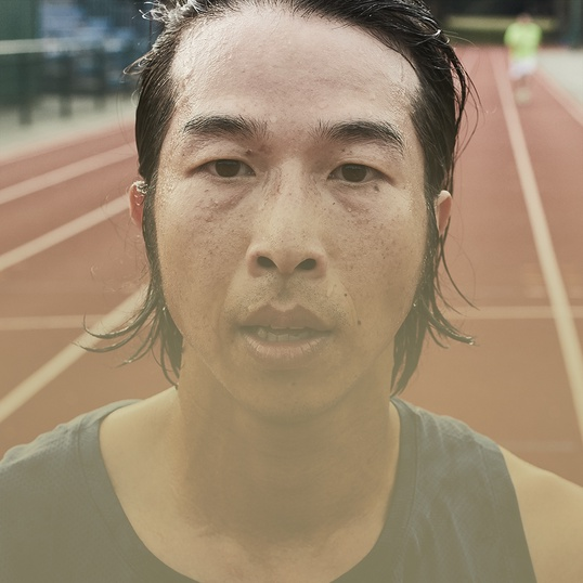 Close up of a man's face while he is standing on a track after running