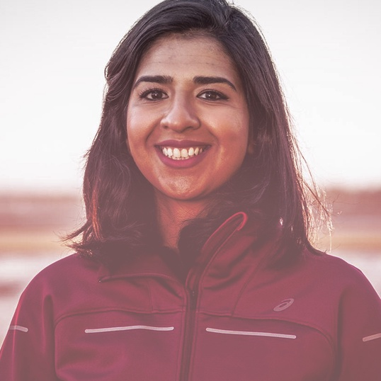 Close up of a woman smiling in an ASICS jacket