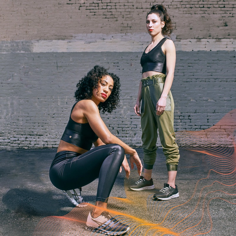 A woman crouching next to a woman standing against a brick wall. Both women are wearing apparel from the New Strong™ Apparel Collection.