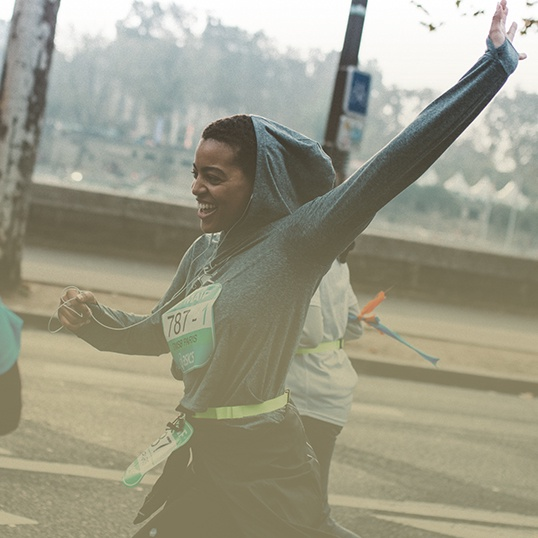 Woman running and lifting her arms up in celebration