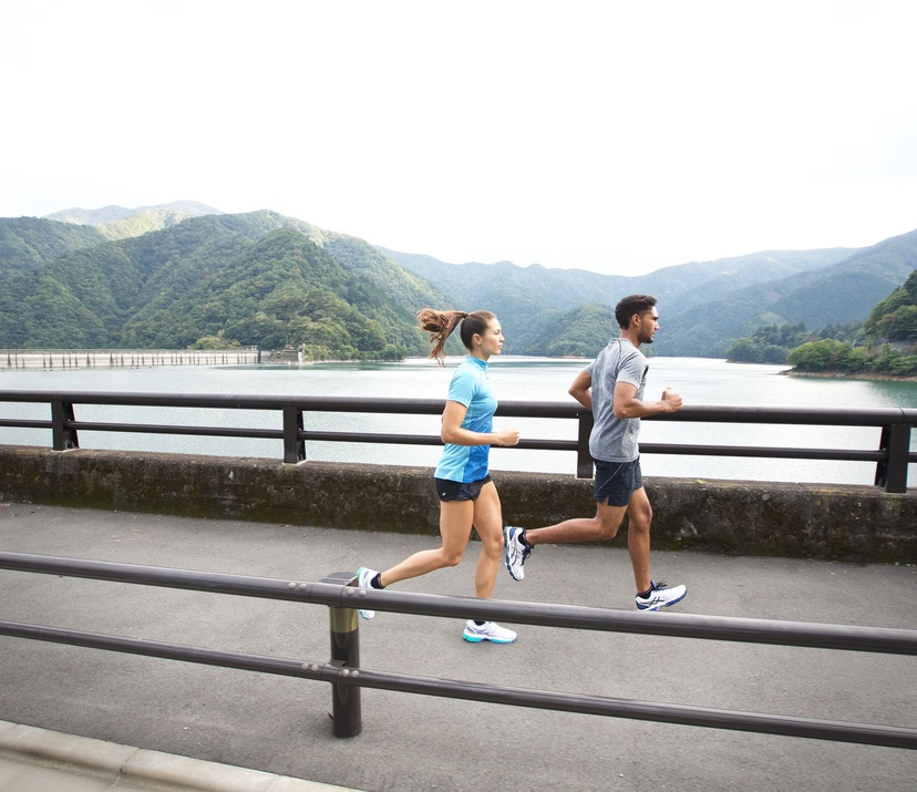 4 reasons to start walking - a girl and guy running on a bridge next to a lake