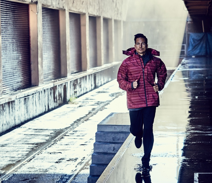 5 ways to vary your running training plan - guy running through an alley with magenta colored jacket