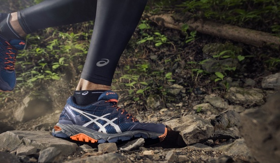 your first running shoes the right pair for you- person trail running with dark blue asics running shoes
