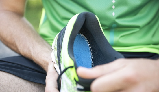 how to choose walking gear - someone holding green running shoes