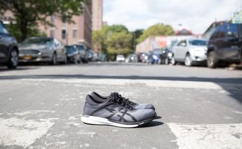 top 10 tips for runners on race day - shows a pair of grey asics shoes in the middle of the road