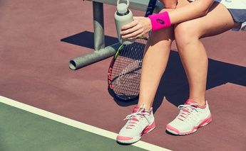 after the match - cool down for tennis players - girl holding a water bottle on the tennis court