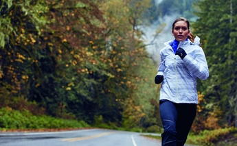 how to train for an autumn running event - woman running on street wearing white striped jacket