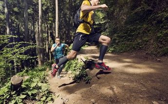 man & woman trail running - turning a corner; woman in teal shirt; man in yellow shirt