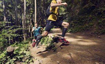 man & woman trail running - turning a corner; woman in teal shirt; man in yellow shirt