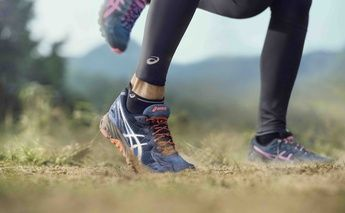 Feet and legs of two women athletes in ASICS leggings and ASICS trainers, running in the desert.