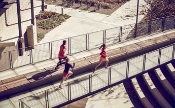 two women & 1 man running across a bridge - top view