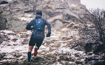 back view of man trail running with backpack