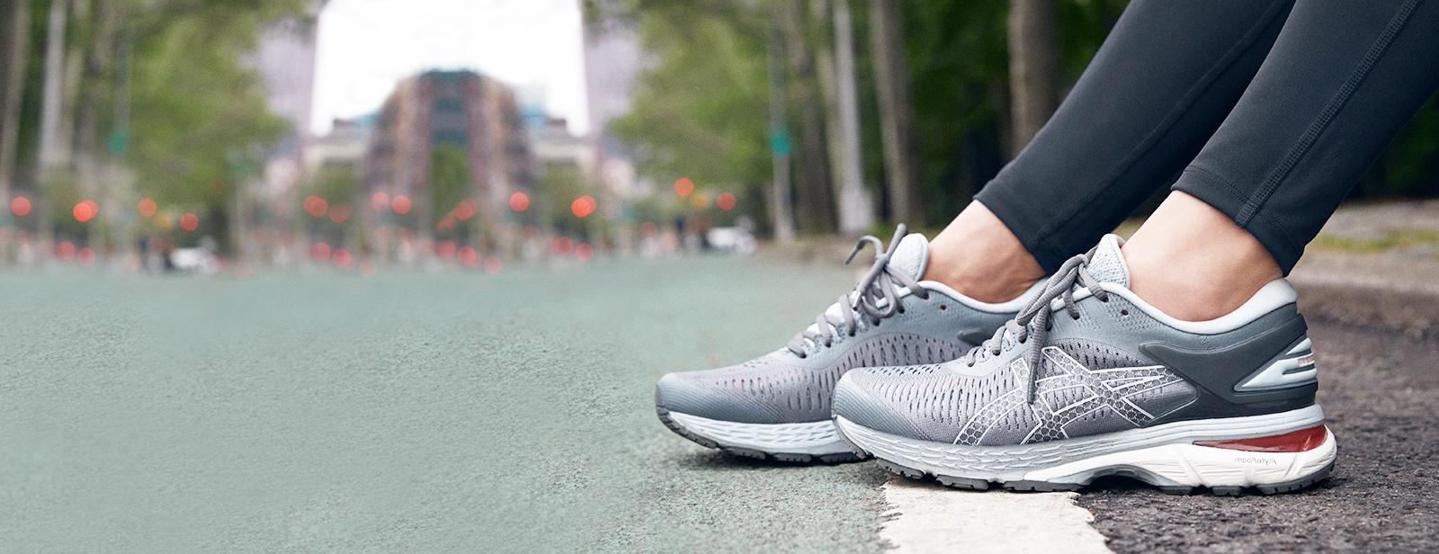 Closeup of gray running shoes on a woman sitting outside on a curb.