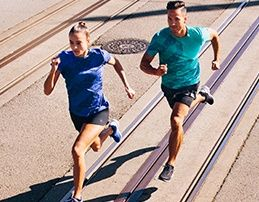 Man and woman running fast on pavement.
