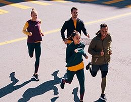 Four people running together outside.
