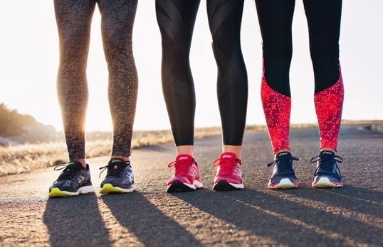 Closeup of three pairs of legs wearing leggings and running shoes at sunset.