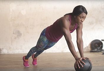 Woman doing a plank on a medicine ball.