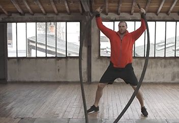Man doing jumping jacks while holding ropes.