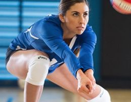 Woman bumping a volleyball.