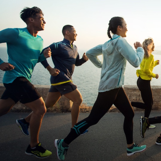 A group of people in athletic gear running and smiling on a path by a waterfront.