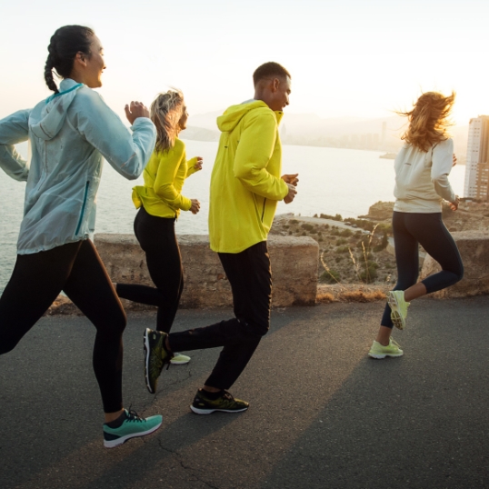 A group of people in athletic gear running and smiling outside at sunset.